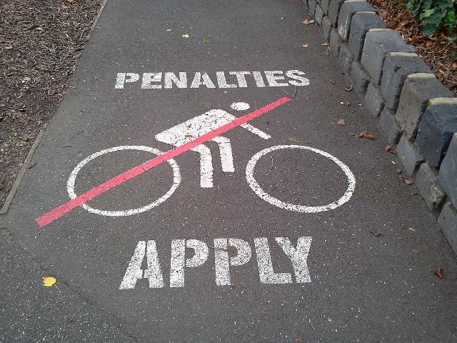 Bicycle warning sign: 'Penalties Apply'